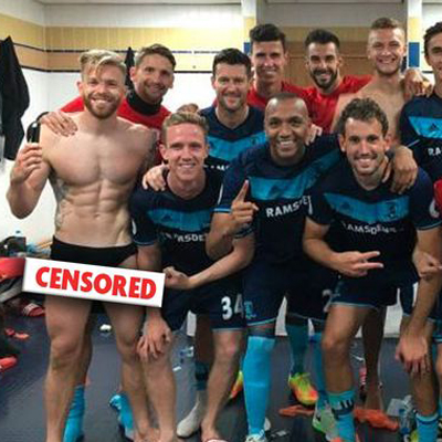 UK: Soccer player poses for a dressing room celebration pic - with his sac hanging out.